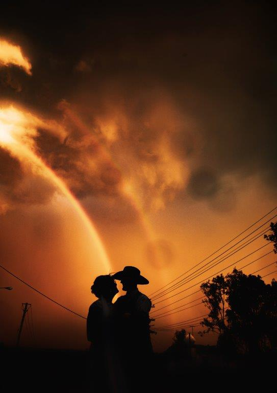 Silhouette bride and groom, rainbow sunset